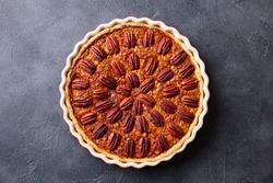 Pecan pie, tart in baking dish. Traditional festive Thanksgiving dessert. Dark background. Top view.