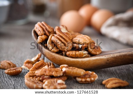 Pecans in a wooden spoon - stock photo