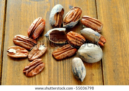 pecans, whole and broken lie on the background of a wooden table