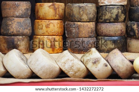 Pecorino cheese wheels with different seasoning arranged geometrically in the window of a delicatessen food shop