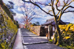 Pedestrial walking street in Ohara village between old stone walls covered by moss - traditional japanese landscape near Kyoto.