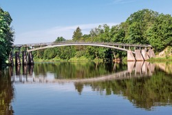 Pedestrian arched bridge over a wide river with calm flow on a sunny summer day. Ogre River.