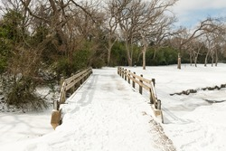 Pedestrian bridge over frozen creek near White Rock Lake that is covered in snow after severe snow storm in Dallas Texas in 2021