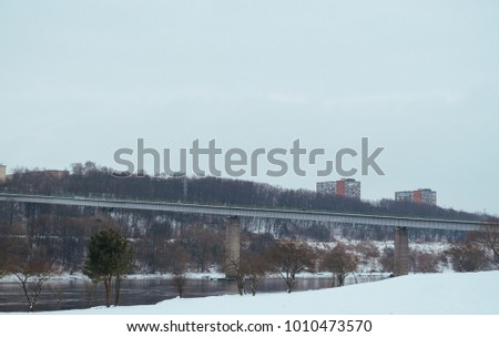 Pedestrian bridge over the river and two red block houses in the winter #1010473570