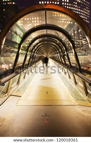 pedestrian bridge under a glass dome in La Defense, Paris, with blurred business people walking at the end of the tunnel
