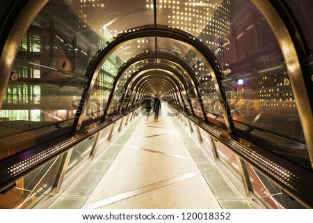 pedestrian bridge with glass dome in La Defense, Paris, at night, and walking business people in motion blur