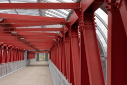 Pedestrian crossing, construction of red metal structures. The roof is made of steel channels connected to each other. Red iron beams on bolts and rivets.