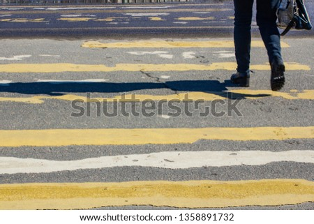 pedestrian crossing on the road with blurred silhouettes of pedestrians and cars #1358891732