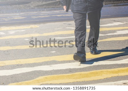 pedestrian crossing on the road with blurred silhouettes of pedestrians and cars #1358891735