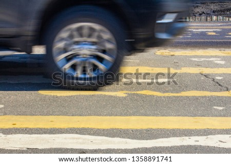 pedestrian crossing on the road with blurred silhouettes of pedestrians and cars #1358891741