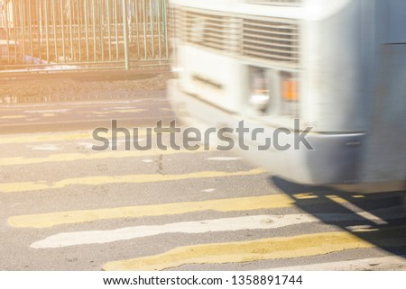 pedestrian crossing on the road with blurred silhouettes of pedestrians and cars #1358891744