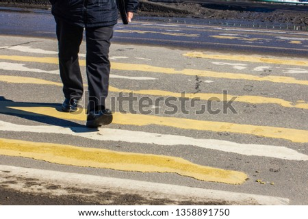 pedestrian crossing on the road with blurred silhouettes of pedestrians and cars #1358891750