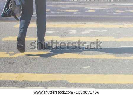 pedestrian crossing on the road with blurred silhouettes of pedestrians and cars #1358891756