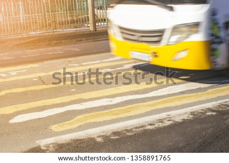 pedestrian crossing on the road with blurred silhouettes of pedestrians and cars #1358891765