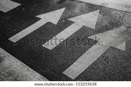 Pedestrian crossing road marking with white arrows on asphalt