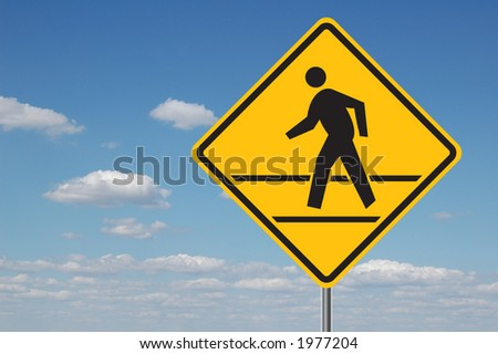 Pedestrian crossing sign with clouds in the background