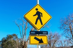Pedestrian crossing sign with flashing lights. Crosswalk beacon provides advance notice of pedestrian activity for drivers.
