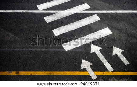 Pedestrian crossing with road marking: white arrows and rectangles on the dark asphalt road