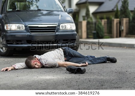 Pedestrian hit by a car lying on the street