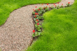 pedestrian path from small gravel in the garden, along the flower bed with red flowers, green grass, selective focusing