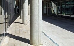 Pedestrian street among two glass wall with a concrete colonnade. Tiled pavement. Background for copy space