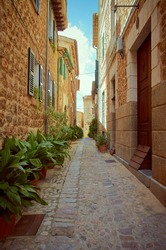 Pedestrian street in a small town. The street is made of stones and the houses too. Green plants, doors and windows. It is summer in Mallorca, Spain.