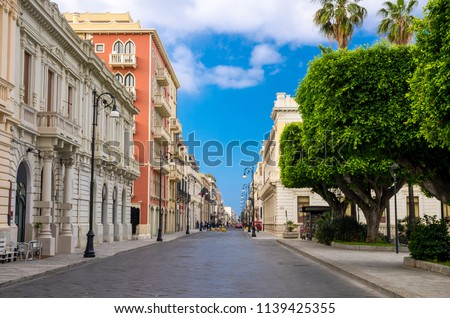 Pedestrian tourist street Corso Giuseppe Garibaldi with old traditional buildings, lamps and green trees in historical centre of the city Reggio di Calabria, Southern Italy