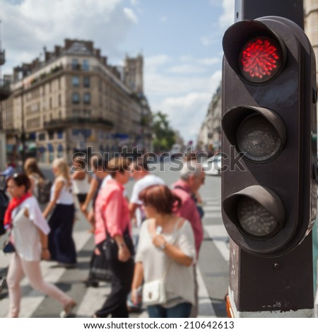 pedestrian traffic lights at a pedestrian crossing with blurred people in Paris
