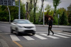 Pedestrian walking on zebra crossing and a driving car failing to stop in blurred motion. Pedestrian reacts with hand to the driver.