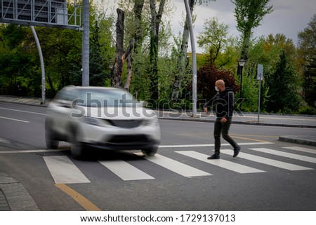 Pedestrian walking on zebra crossing and a driving car failing to stop in blurred motion. Pedestrian reacts with hand to the driver.  Foto stock ©