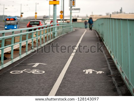 pedestrian walkway and bicycle path on bridge with busy traffic