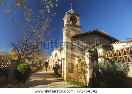 Pedestrian Walkway and Cathedral Bell Tower in Spanish Arts and Crafts Village in Sedona under warm late Autumn Sunshine