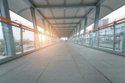 Pedestrian Walkway covered metallic city crosswalk. ground view of corridor interior of pedestrian overpass tunnel with morning sunrise