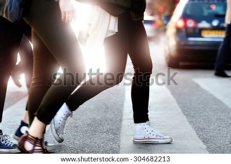 Pedestrians crossing street against bright light