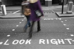 Pedestrians crossing the road; The Look right  signage on the asphalt road, slow, at zebra crossing