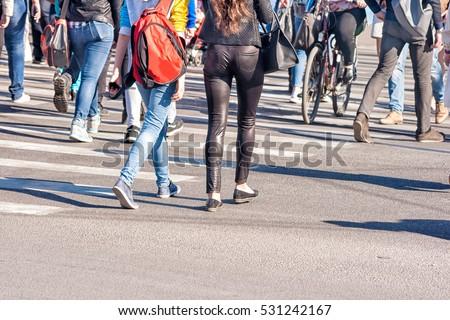 pedestrians walking on a pedestrian crossing on sunny day