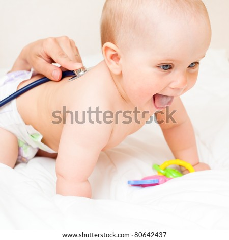 Pediatric doctor exams little baby girl with stethoscope
