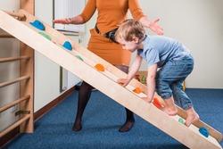 Pediatric Sensory Integration Therapy - a boy on climbing wall