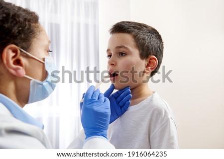 Pediatrician examining little boys throat to diagnose his illness. Zdjęcia stock ©