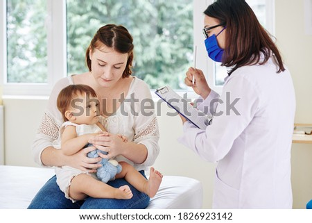 Pediatrician in medical mask talking to baby girl and taking notes in medical card Stockfoto ©