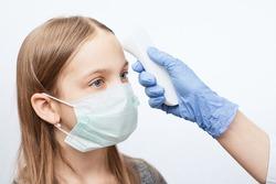 Pediatrician or doctor checks elementary age girl's body temperature using infrared forehead thermometer (thermometer gun) for virus symptom - epidemic coronavirus outbreak concept