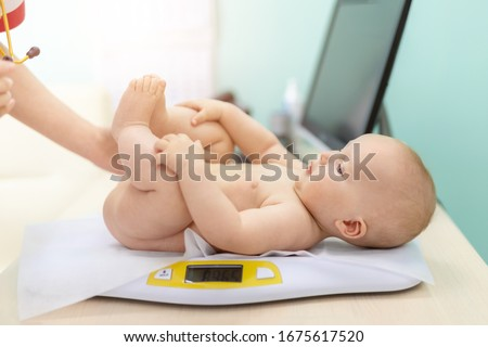 Pediatrician specialist taking measurement infant child weight during screening examination. Cute caucasian baby lying on electronic scales doctors office. Children healthcare and disease prevention Photo stock ©