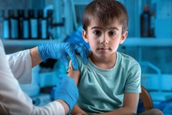 pediatrician vaccinating child in the pediatric clinic / doctor injecting vaccine preventive to little boy in the hospital