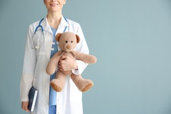 Pediatrician with toy on color background
