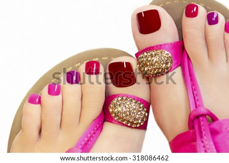 Pedicure with different colors of paint on a woman's feet in pink sandals on a white background.