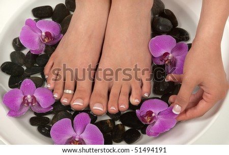 Pedicured feet, manicured hand  and orchids