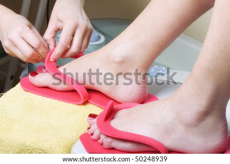 Pedicurist fastening pink slippers on woman foot closeup photo