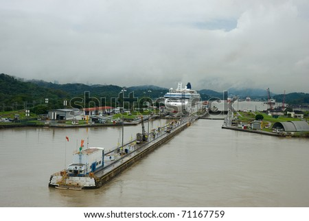 Pedro Miguel locks. Panama city buildings can be seen behind the hills in the background as well as the Miraflores locks.