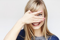 Peeking young blond woman smiling at camera