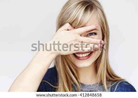 Peeking young blond woman smiling at camera